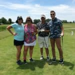 four people posing while golfing